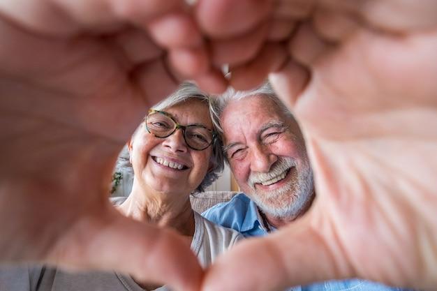 Paar twee oude en gelukkige senioren die thuis plezier hebben op de bank en een hartvorm doen met hun handen en vingers die naar de camera kijken.