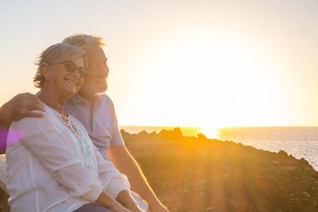 Paar twee schattige senioren die samen genieten van de zomer en plezier hebben op het strand, kijkend naar de zee of de oceaan met zonsondergang - volwassen mensen met een goede levensstijl