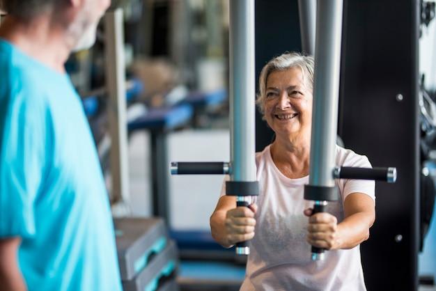 Paar twee senioren in de sportschool die samen trainen - vrouw doet een oefening in een machine en de volwassen man kijkt naar haar - glimlacht en heeft plezier