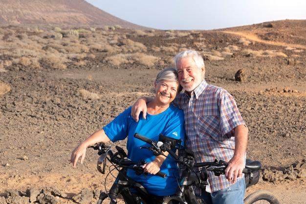 Paar twee senioren omhelsden elkaar in de bergen op hun fiets - gelukkige gepensioneerden die samen met liefde en genegenheid naar de camera kijken