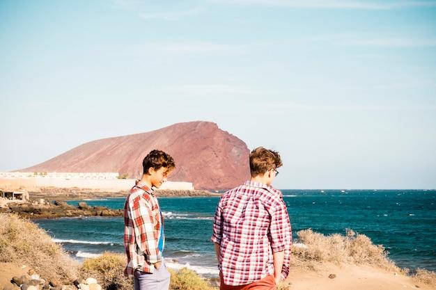 Paar twee tieners met een vriendschap op het strand die naar de zee kijken en samen praten - zee of oceaan op de achtergrond