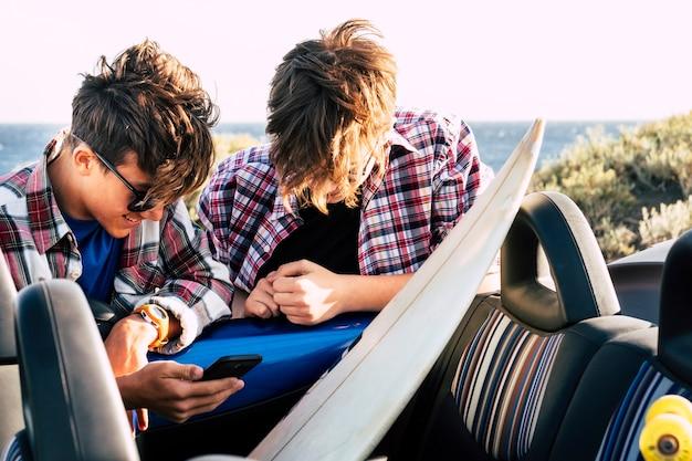 Paar twee tieners samen in het park of op het strand bij de auto met surfplank en skateboard - twee mannen met zee op de achtergrond kijken naar wat grappig op dezelfde telefoon