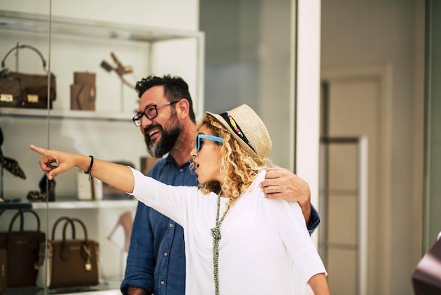 Paar twee volwassenen die samen winkelen en kijken naar de winkels in het winkelcentrum die glimlachen en plezier hebben - vrouw die aangeeft met haar arm
