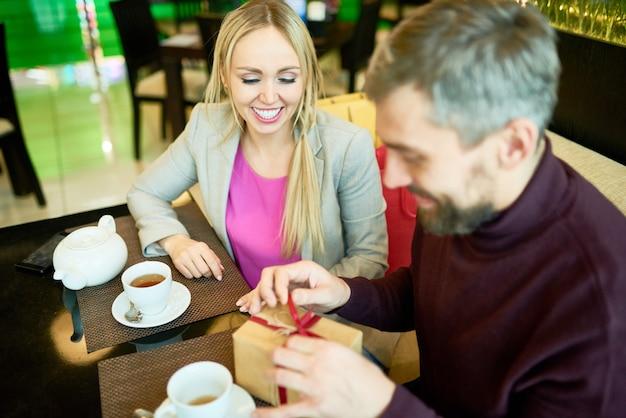 Paar uitpakken presenteert in cafe
