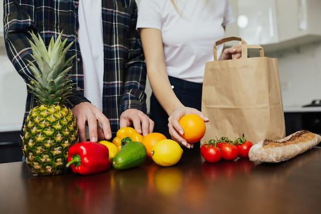Paar uitpakken samen verse producten uit de winkel in de keuken