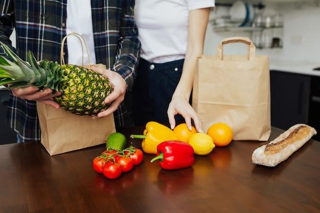 Paar uitpakken van verse producten van de markt op tafel