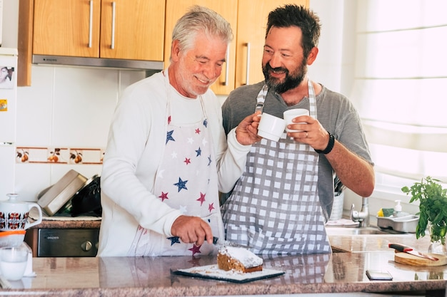Paar vader en zoon verschillende gemengde leeftijden en generaties thuis doen een taart samen koken in de keuken met geluk en plezier samen in vriendschap