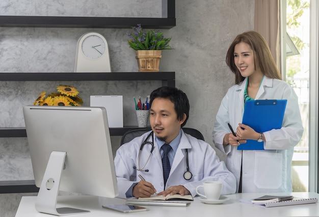 Paar van aziatische artsen die met collega werken die technologiecomputer met behulp van