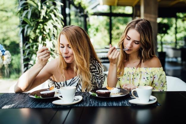 Paar van dougter en moeder die dessert eten in modern restaurant?