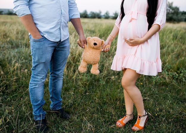 Paar van een man en een zwangere vrouw die een teddybeerstuk speelgoed houden