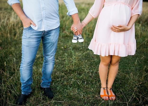 Paar van een man en een zwangere vrouw die kleine babyslofjes houden