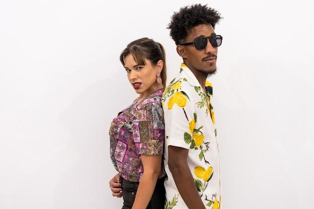 Paar van een zwarte jongen en een blank meisje op een witte achtergrond, bloemrijke overhemden, modieus geposeerd met hun rug tegen elkaar gedrukt
