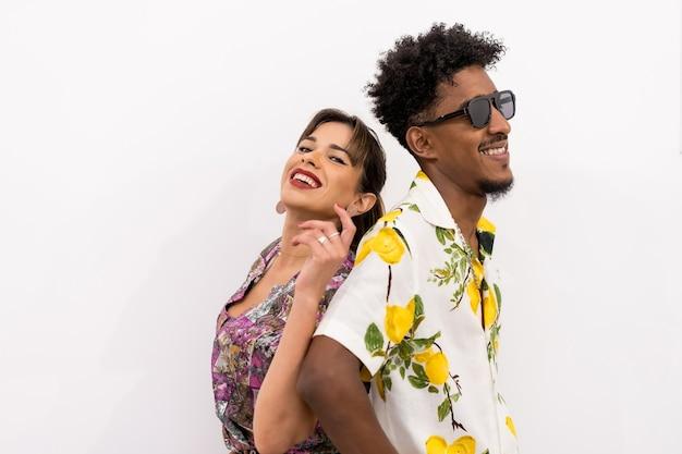 Paar van een zwarte jongen en een blank meisje op een witte achtergrond, bloemrijke shirts, glimlachend in een modieuze pose met hun rug tegen elkaar gedrukt