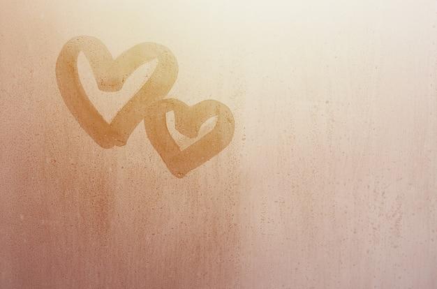 Paar van het abstracte vage die symbool van het liefdehart met de hand op het natte vensterglas met zonlichtachtergrond wordt getrokken.