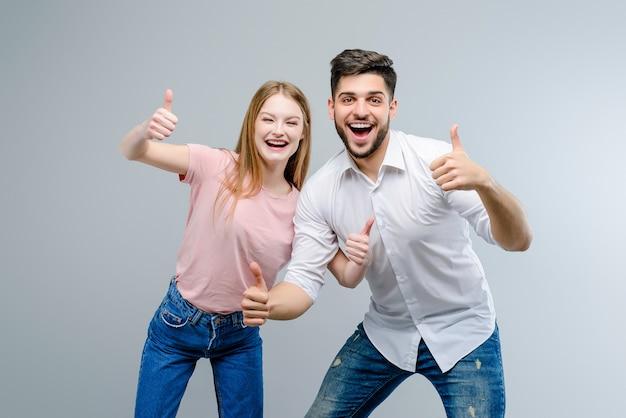 Paar van jonge man en vrouw die omhoog geïsoleerde duimen tonen