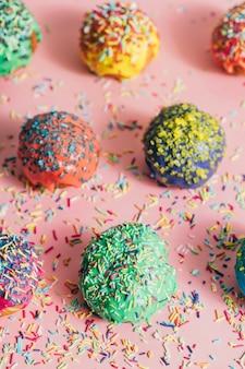 Paar van kleurrijke bestrooid donuts op een roze achtergrond