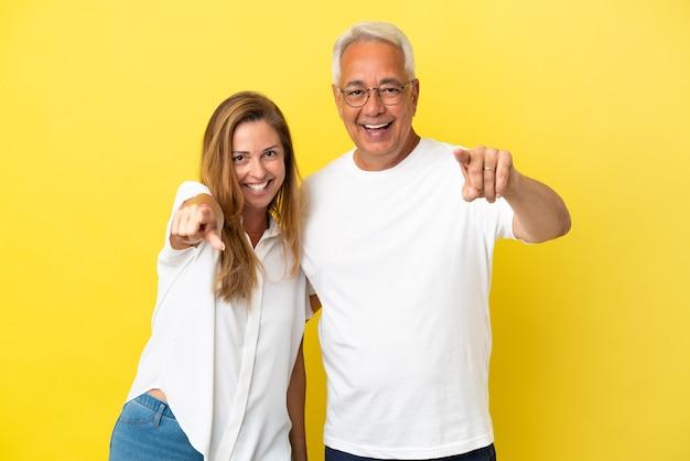 Paar van middelbare leeftijd geïsoleerd op gele achtergrond wijst vinger naar voren