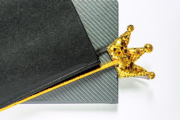 Paar van persoonlijke planners en wonder stick met gouden kroon gemaakt van pailletten geïsoleerd op een witte achtergrond.