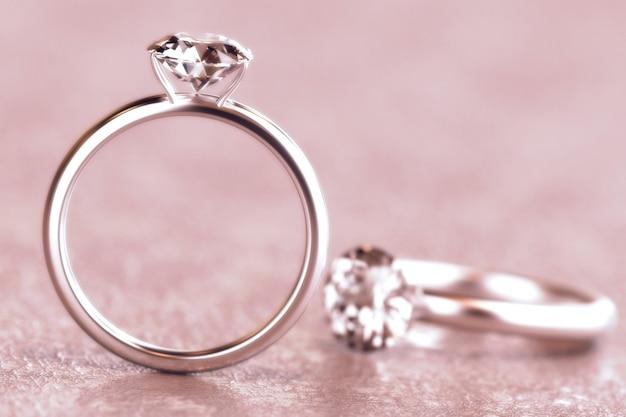 Paar van rond diamond cut ring isolated op roze achtergrond, het 3d teruggeven.