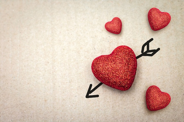 Paar van rood hart met cupidpijl op kartonachtergrond.