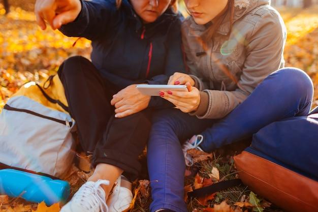 Paar van toeristen met rugzakken die naar juiste manier zoeken die navigator in de herfstbos gebruiken