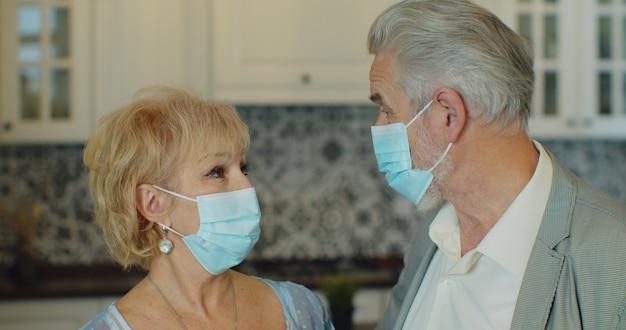 Paar van twee senioren met medisch masker om coronavirus te voorkomen.