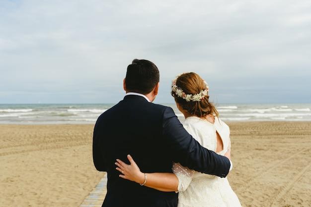 Paar van vet pasgetrouwden knuffelen elkaar