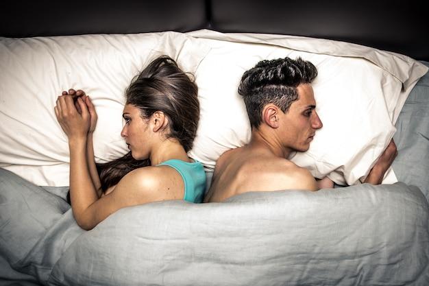 Paar vechten in bed en de andere kant op draaien