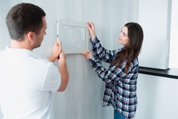 Paar verhuisde naar een nieuw huis. close-up foto van vrouwelijke handen tijdens het inrichten van een nieuw appartement en het ophangen van een foto of fotolijst aan de muur