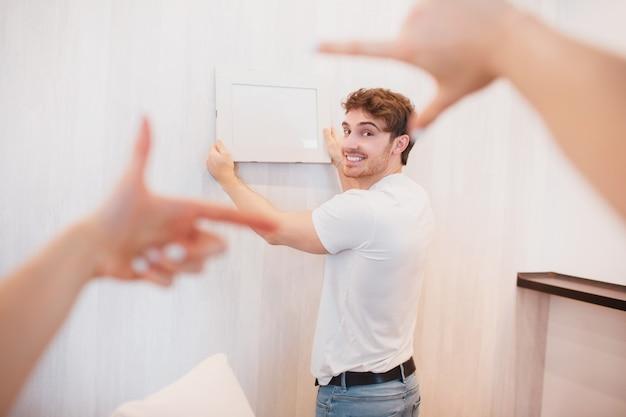 Paar verhuisde naar een nieuw huis. close-up foto van vrouwelijke handen tijdens het versieren van nieuw appartement, man opknoping foto of fotolijst aan de muur
