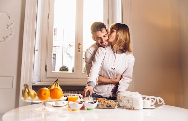 Paar verliefd eten 's ochtends vroeg in de keuken thuis en hebben een goede tijd.