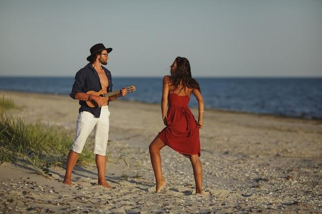 Paar verliefd gitaar spelen en dansen op het strand