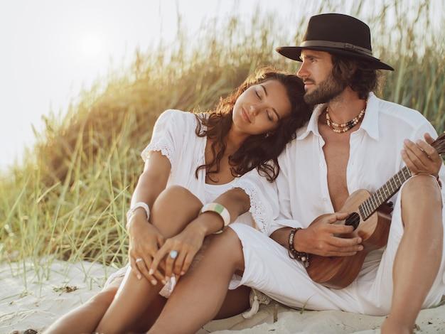 Paar verliefd gitaar spelen en rusten op het strand