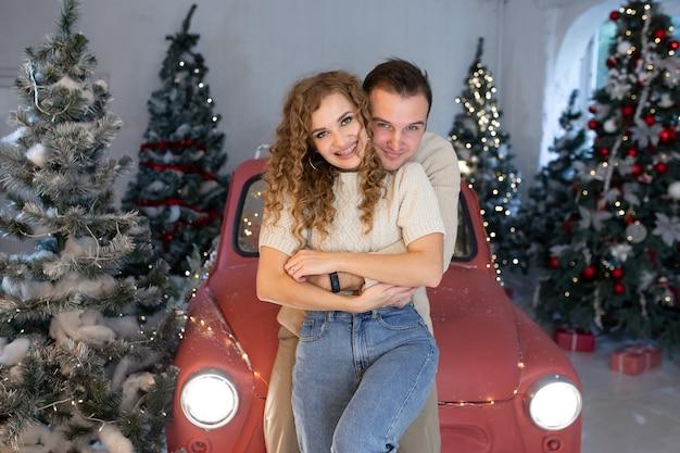 Paar verliefd in de buurt van mooi versierde kerstboom en rode auto