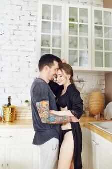 Paar verliefd in de keuken in de ochtend knuffels en bereidt ontbijt. gelukkig gezinsleven. vreugde en glimlach op het gezicht van mannen en vrouwen. liefde en relaties