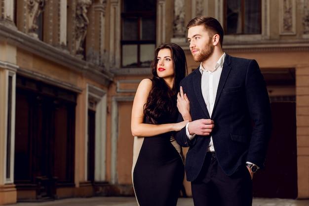 Paar verliefd in elegante outfit wandelen in de oude stad straat. vrij donkerbruine vrouw met rode lippen en haar knappe vriend hebben vrije tijd.