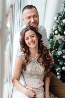 Paar verliefd in feestelijke kleding zitten in de buurt van de kerstboom