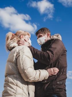 Paar verliefd in jassen en medische maskers