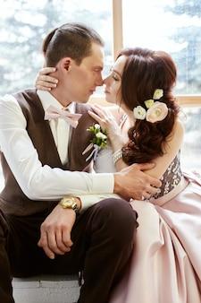 Paar verliefd in mooie kleren en een groot boeket bloemen in de buurt van een groot raam. liefdesverhaal. knuffels kussen en emoties op het gezicht van een liefdevol stel Premium Foto