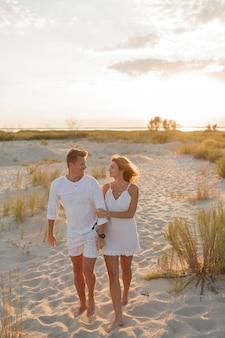 Paar verliefd in witte kleren wandelen op het strand. volledige lengte.