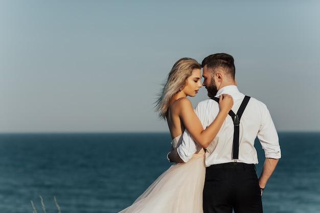 Paar verliefd jonge bruid en bruidegom knuffelen op het oppervlak van de blauwe zee op hun trouwdag in de zomer.