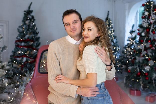 Paar verliefd knuffelen in de buurt van rode auto en mooi versierde kerstboom, genietend van de kerstmagie.