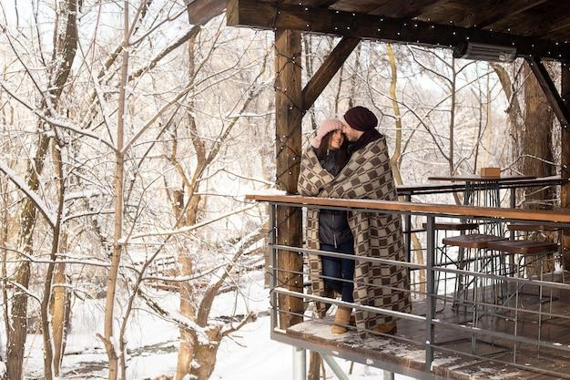 Paar verliefd knuffelen in het park in wintercafé