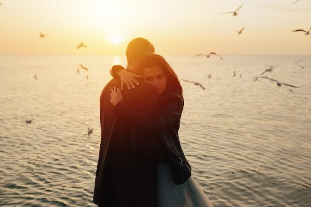 Paar verliefd knuffelen op het strand bij zonsondergang met vliegende meeuwen op de achtergrond.