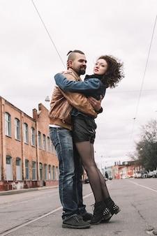 Paar verliefd knuffelen staande op straat van de stad