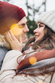 Paar verliefd knuffels en kusjes in een winter naaldbos
