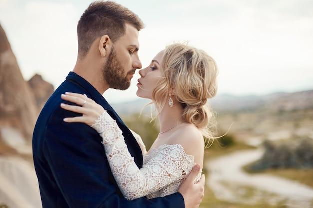 Paar verliefd knuffels en kusjes in fantastische bergen in de natuur. meisje in lange witte jurk met boeket bloemen in haar handen, man in jas. bruiloft in de natuur, relaties en liefde