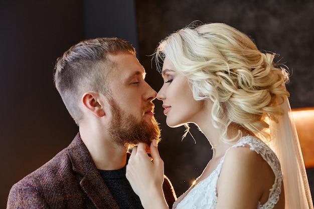 Paar verliefd knuffels en kusjes op hun trouwdag. hipsterbruidegom en de bruid, liefde en loyaliteit. het ideale koppel bereidt zich voor om man en vrouw te worden. man en vrouw die elkaar dicht bekijken