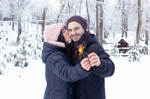Paar verliefd kussen en houden schittert in park met sneeuw
