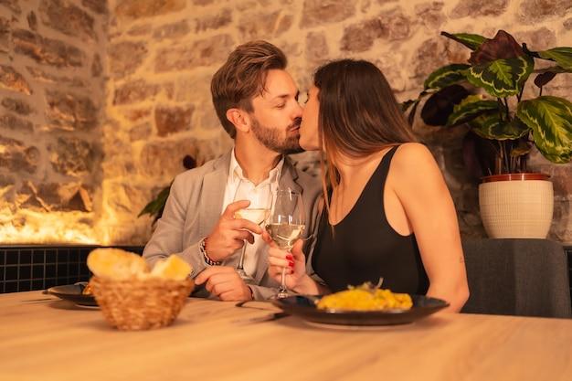 Paar verliefd kussen in een restaurant, met plezier met diner samen met eten